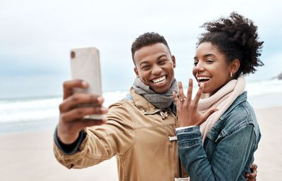 Young couple taking a selfie at the beach with woman showing off engagement ring