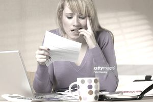 Woman at her desk chewing her nails as she reads a bill/notice