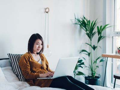 Young woman working on laptop in bedroom