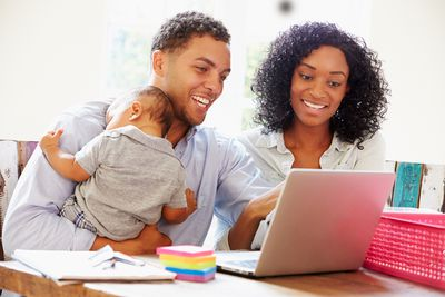 a young couple and their baby browsing online on a laptop