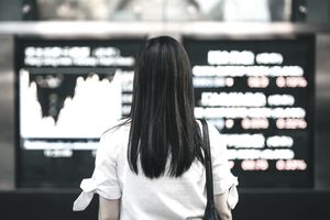 Woman reading stock market exchange display, representing trading commodities.