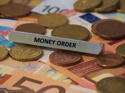 Money order sign sitting atop assorted foreign currency