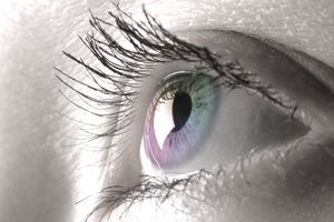 Close-up a woman's eye in a rainbow of colors representing biometric technology