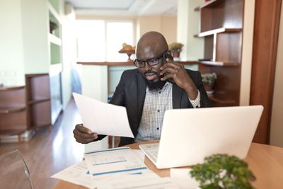 Man with glasses on phone while working on a laptop