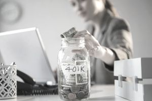 Businesswoman Putting Money Into 401(K) Jar at Desk