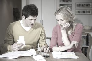 Young couple with receipts and documents using calculator to pay themselves first before business expenses