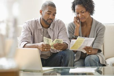 A couple sitting on sofa with laptop, paying bills
