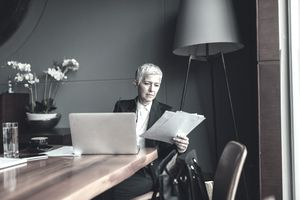 Businesswoman looking at paperwork in an office with a laptop