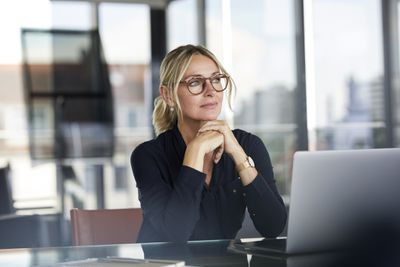 Bespectacled woman sitting in front of laptop