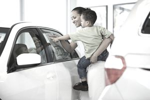 A person holding a toddler looks at the sticker on a new car.