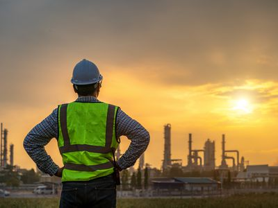 Asian engineers looking at site in oil and gas refinery or Petrochemical factory during sunrise, industrial concept.