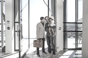A couple stands with their baby in front of a large glass door.