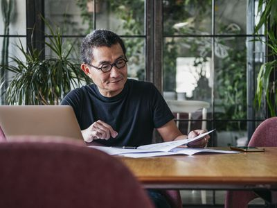asian man sitting at table going through paperwork on computer