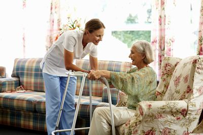A nurse helps an older woman from a chair.