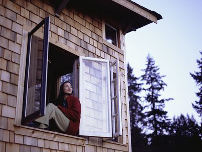 A woman in red flannel sits in the open window of a cabin and gazes out with an expression of supreme contentment.