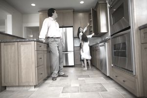 A family inspects the kitchen in a new house for sale