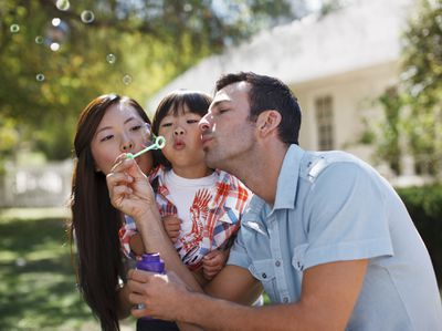 family blowing bubbles in front of their house