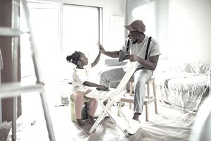 Father painting a chair with his daughter.
