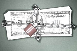 A stack of $100 bills tied up with a chain and a small padlock
