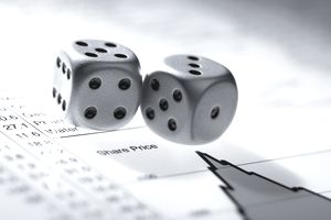 Silver dice on a list of share prices representing the several risk an investor can face.