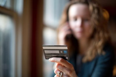 Woman's Hand Holding a Credit Card With Her Unfocused Image in Background, Holding Cellphone