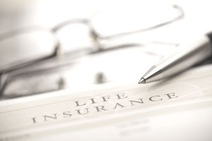 Life insurance policy with a pen and eyeglasses