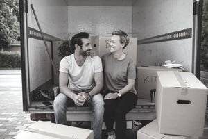 A couple smiles at each other while sitting by cardboard boxes in a U-Haul moving truck