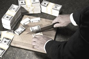 Person cutting up stacks of money using a sharp knife indicating a fiscal year budget