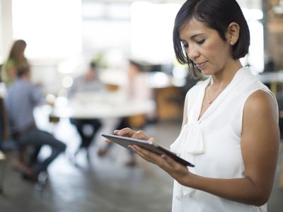 A woman in an office setting looks at a tablet