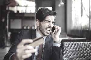 Man shouting angrily into phone while holding a credit card