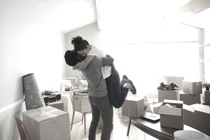 Enthusiastic, affectionate couple hugging in new home, unpacking cardboard boxes