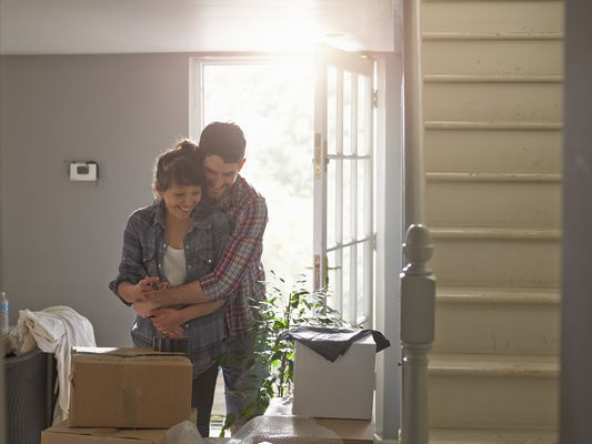 Young couple embracing in new home with boxes in front of them