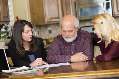 Professional advisor seated at kitchen table with a married couple, reviewing documents