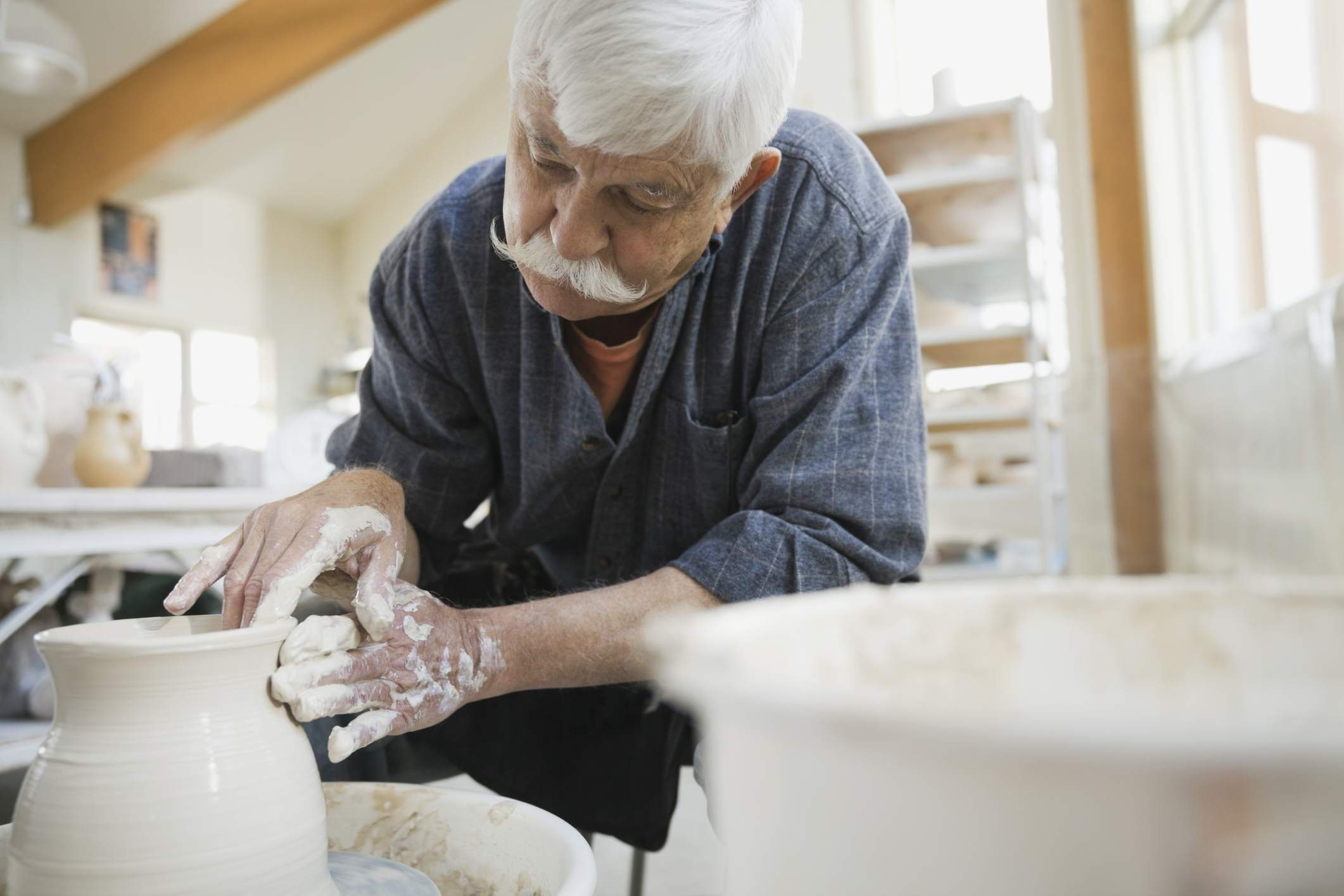 senior man working with clay to make pot