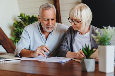 A mature couple signs paperwork at their kitchen table.