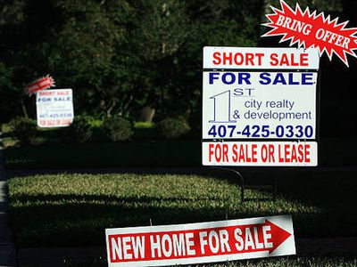 Two homes side by side with lawn signs advertising Short Sale on home, asking buyers to bring offers
