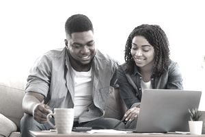 A man and a woman review paperwork in front of a laptop