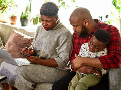 Couple with young son seated on couch with laptop and mobile