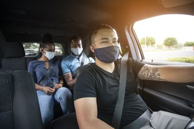 A rideshare driver wears a mask while driving two passengers, who are also wearing masks