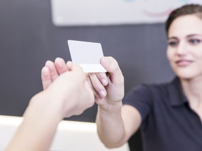 Patient giving credit card to receptionist of dental surgery