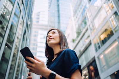 A young woman reviews her investments on her phone while standing in front of skyscrapers.