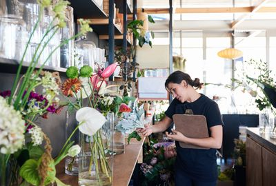 Female florist stands in shop while talking on phone