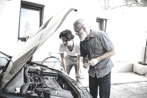 Hispanic grandson repairing the car with his caucasian grandfather