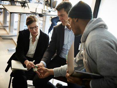 Male entrepreneur showing solar toy car to bank managers during meeting in creative office