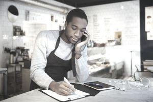 A young Black businessman speaks on the phone while leaning on a counter and takes notes in a notebook.