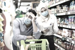 Unhappy Muslim Couple Calculating Prices Doing Grocery Shopping in Supermaket
