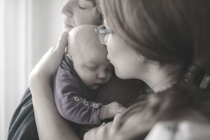 Two women hold their newborn baby while considering whether they need life insurance