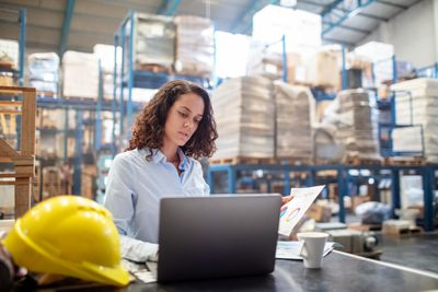 Woman working on laptop in a warehouse