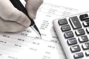 Man reviewing financial document with calculator