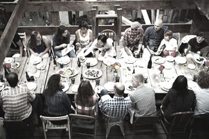 A group of people gather at their communal living area's dining table to share a meal